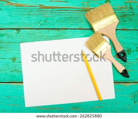 Working tools. Paper with pencil and the working tools on wooden, green background. - stock photo