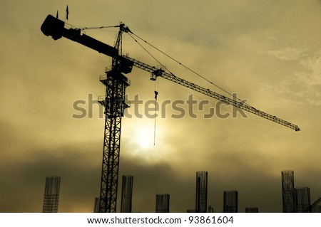 Working tower crane at late evening in silhouette. - stock photo