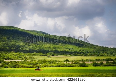 Working Tractor at Agricultural Village Field Around Mountains - stock photo