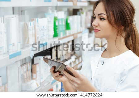 Working using technology. Shot of a charming pharmacist working using a digital tablet looking at the shelves at the  drugstore. - stock photo