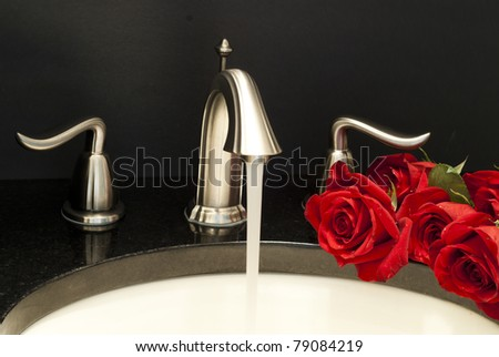 Working water mixer and a few roses on a sink. - stock photo