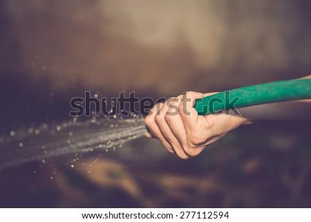 Working watering garden. Vintage filter. - stock photo