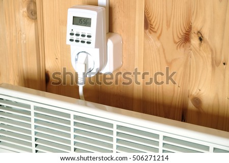 Working white electric convector heater plugged to timer power socket operated in smart house system against wooden wall inside room side view closeup
