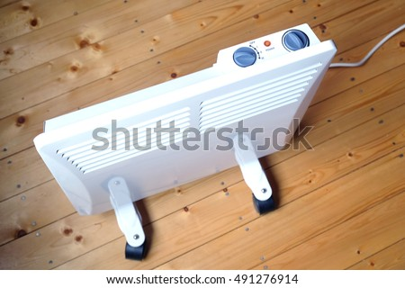Working white electric convector heater with control panel on top on wooden floor in a house room top view closeup