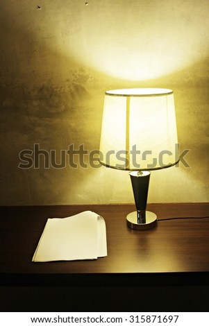 Working with a lamp and paper on the wooden table