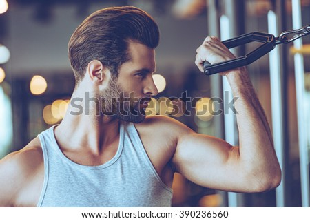 Working with bicep. Close up of young man in sportswear exercising at gym - stock photo