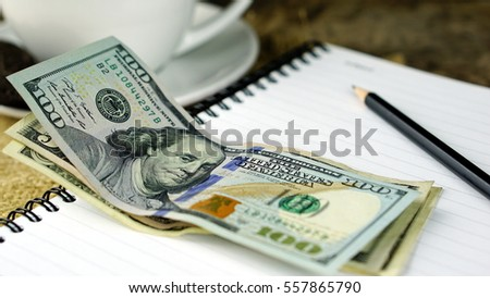Working with Coffee. A cup of latte, cappuccino or espresso coffee with milk put on a wood table with cookies, notebook, pencil and US Dollars Banknote.