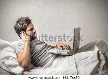Working with Computer in Bed - stock photo