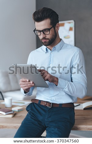 Working with his touchpad. Handsome young man wearing glasses and working with touchpad while leaning to the table in office - stock photo