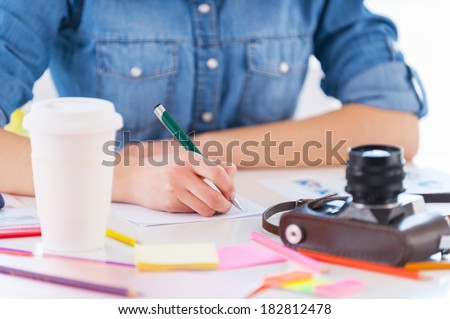 Working with pleasure. Cropped image of young business woman in casual wear sitting at his working place and writing something in his note pad - stock photo