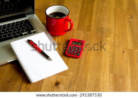 Working with the laptop, taking notes and doing calculations - stock photo