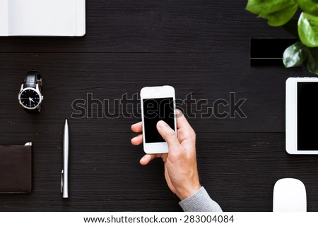 Working with the phone on a black background, overhead view. Man works with the phone that will quickly carry out the work. A touch of the finger on the screen. - stock photo