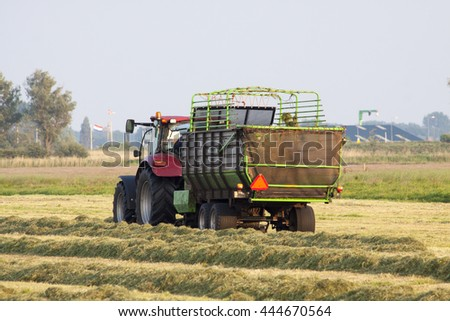Working with tractor on dutch farmland for background use - stock photo