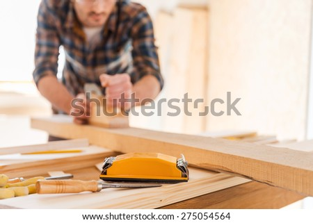 Working with wood. Close-up of male carpenter working with wood in his workshop - stock photo