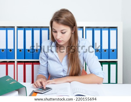 Working woman with blond hair and calculator at office - stock photo