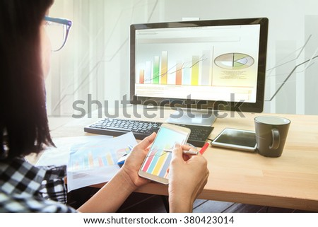 working woman with smart phone in hand looking to computer business report on table top - stock photo