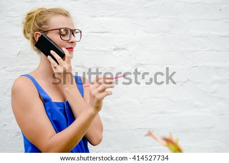 Working young pretty woman talking on smart phone holding pencil in hand pointing - stock photo