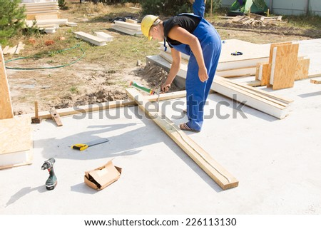 Workman applying wood glue to an insulated wooden beam to be positioned in the corner of the wall on a new build house construction site - stock photo