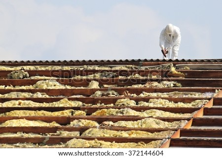 workman at rooftop of building being remediated - stock photo
