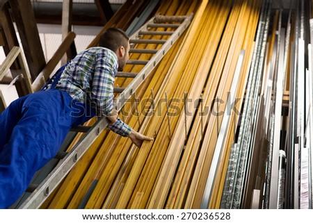 Workman choosing PVC window profile at stand - stock photo