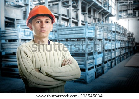 Workman in big storage room with metal boxes in factory - stock photo
