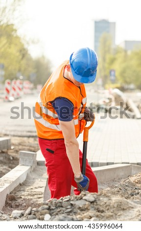 Workman in high-visibility vest using a shovel  - stock photo