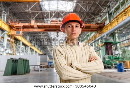 Workman in red helmet in the workshop of machinery plant - stock photo