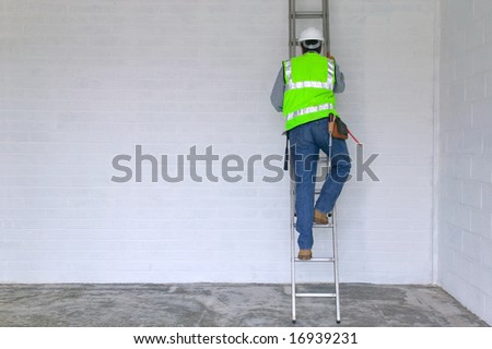 Workman in reflective vest and hard hat climbing a ladder, slight motion blur on the man. - stock photo