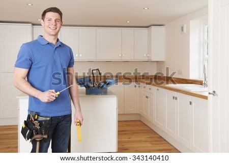 Workman Installing Beautiful Fitted Kitchen - stock photo