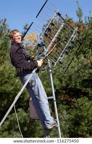 Workman installing HDTV digital antenna on a house