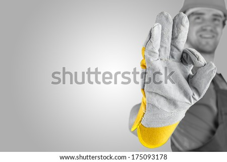 Workman making a perfect gesture with his gloved hand with focus to his hand over a grey background with a highlight and copyspace. - stock photo