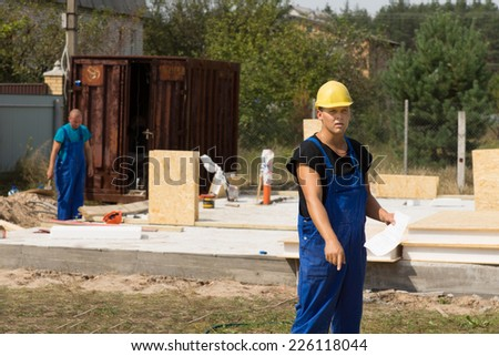 Workman pointing to something on the ground as he stands in his overalls and hardhat holding a document on a building site for a new house - stock photo