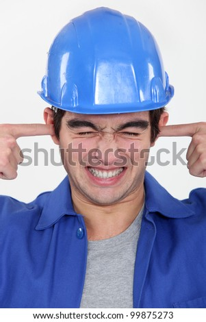 workman putting fingers in his ears to block out noise