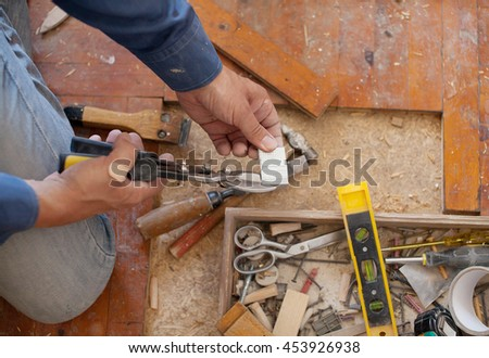 Workman removing old floor. Close up view of his gloved hands