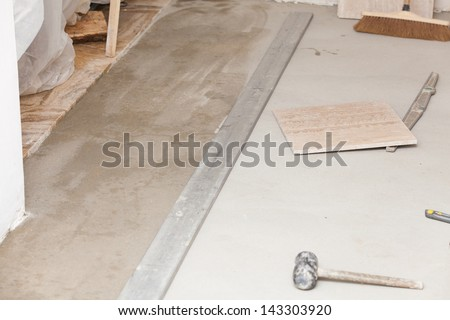 workman's tools on a floor that is being tiled