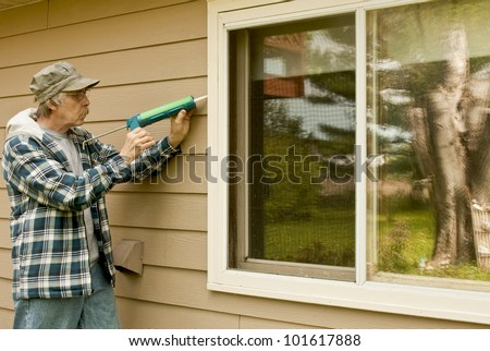 workman sealing an exterior window with caulk to reduce air infiltration - stock photo