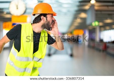 Workman shouting on unfocused background - stock photo