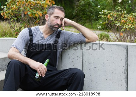 workman sitting outside with a bottle of beer and sleeping
