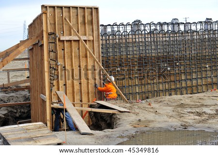 Workman ties reinforcing steel bars to wooden forms prior to pouring concrete on construction project