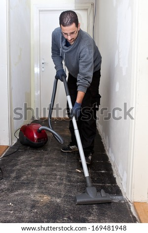 Workman vacuuming a passage during renovations after removing the old floor tiles - stock photo