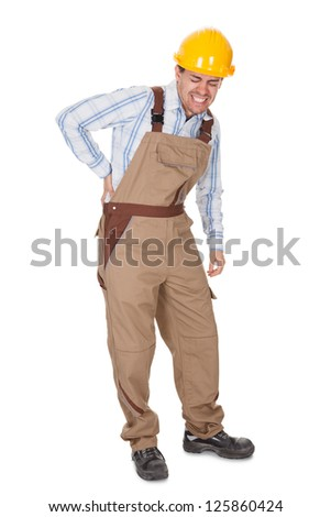 Workman with a back injury grimacing and clutching his lower back with his hand isolated on white - stock photo