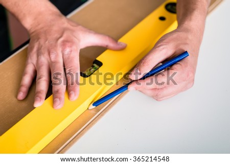 Workman with air level flooring home - stock photo