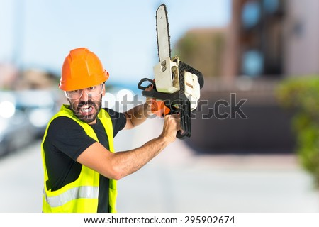 Workman with chainsaw on unfocused background - stock photo