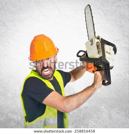 Workman with chainsaw over textured background - stock photo