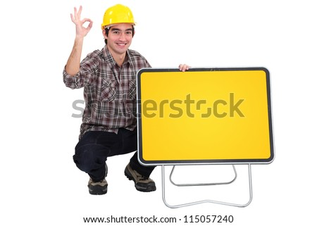 Workman with empty road sign for message - stock photo