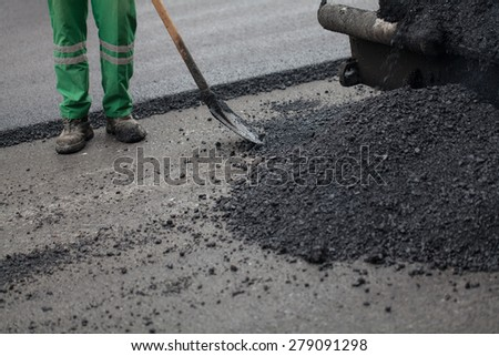 workman with shovel working on new asphalt - stock photo
