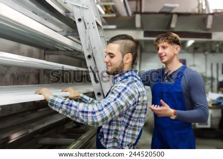 Workmen choosing window profiles at factory - stock photo