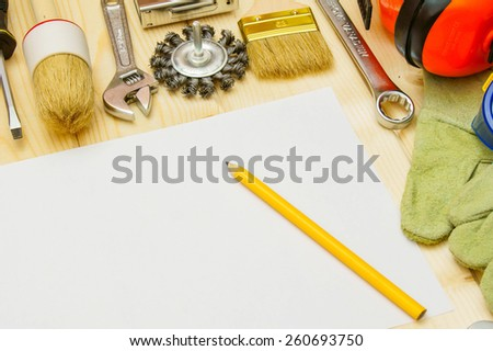 Workng tools. Paper for notes and set of working tools (mallet, wrench, pen and others) on wooden background. - stock photo