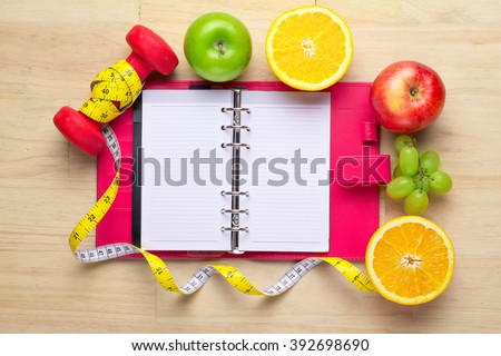 Workout and fitness dieting copy space diary. Healthy lifestyle concept. Apple, dumbbell, and measuring tape on rustic wooden table.  - stock photo