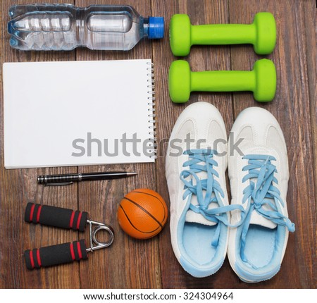 Workout and fitness dieting copy space diary. Healthy lifestyle concept. Dumbbell, water, expander hand and ball on rustic wooden table.